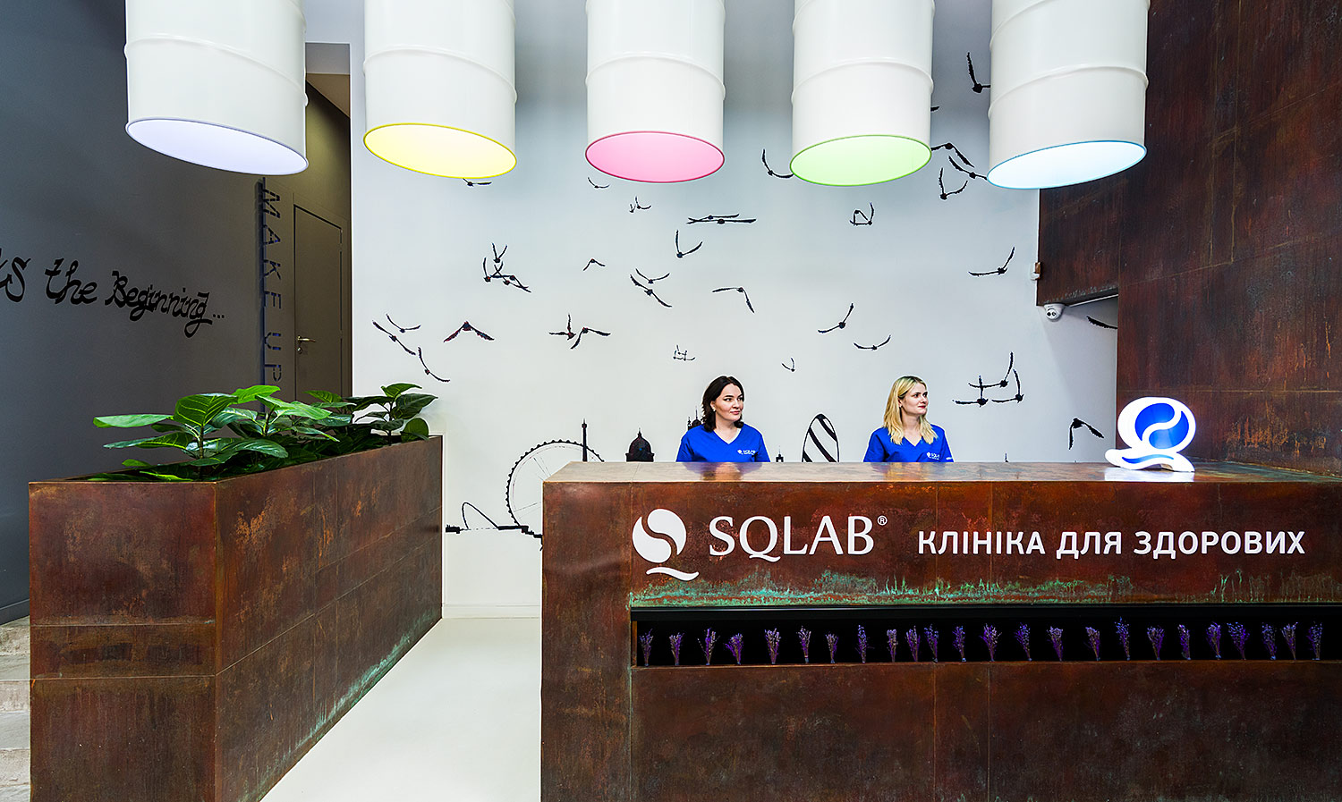 A branded reception desk and a lamp in the shape of a logo. SQLAB is a clinic for healthy people.