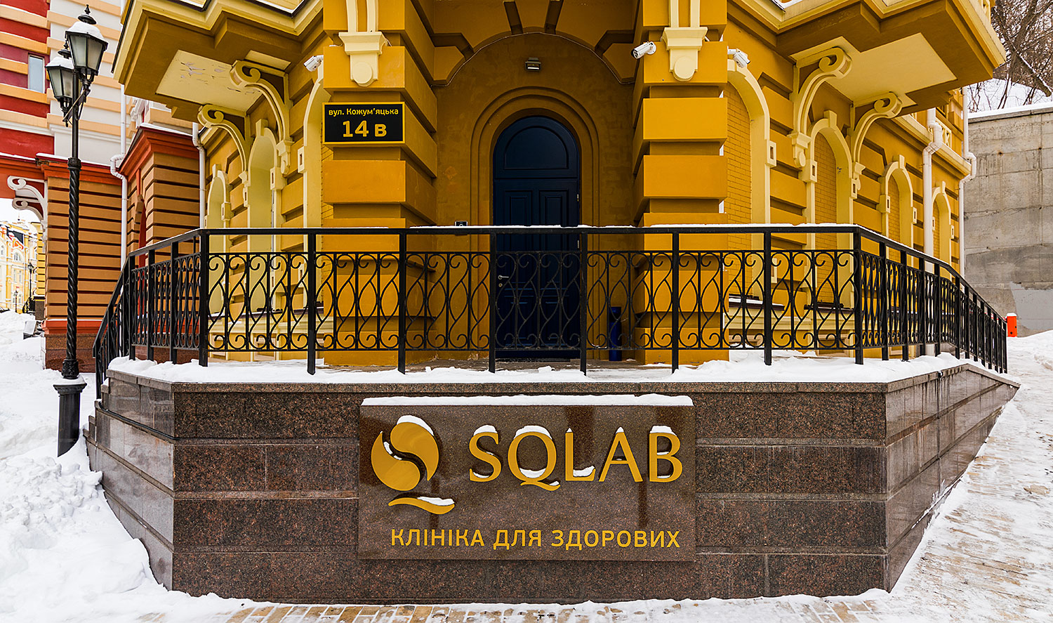 SQLAB clinic exterior signboard logo with backlight. Granite base and golden letters.