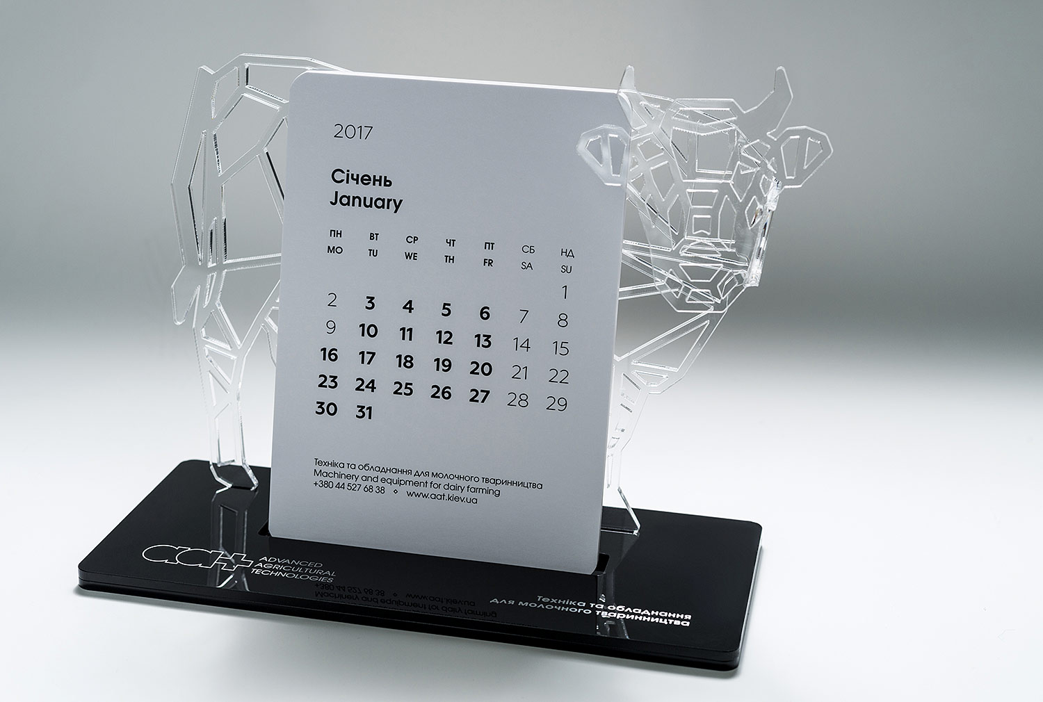 Creative desktop calendar Advanced Agricultural Technologies (aat). Cow as a symbol of dairy farming. Stylish acrylic stand for calendar sheets and note papers.