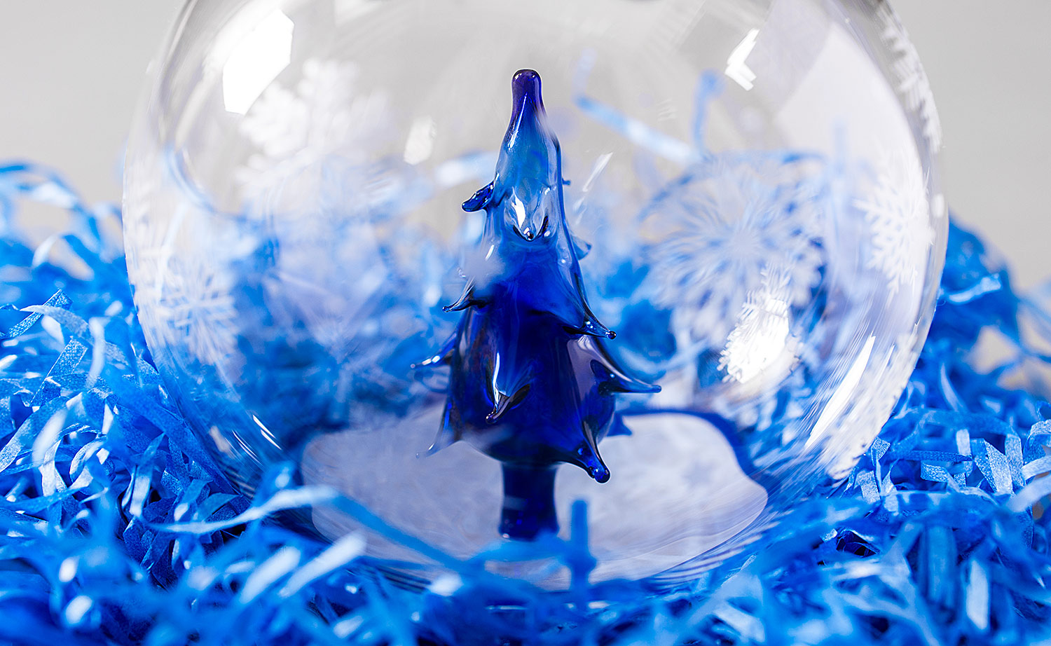 Blue glass Christmas tree inside a transparent glass ball. The magic craft of glassblower.