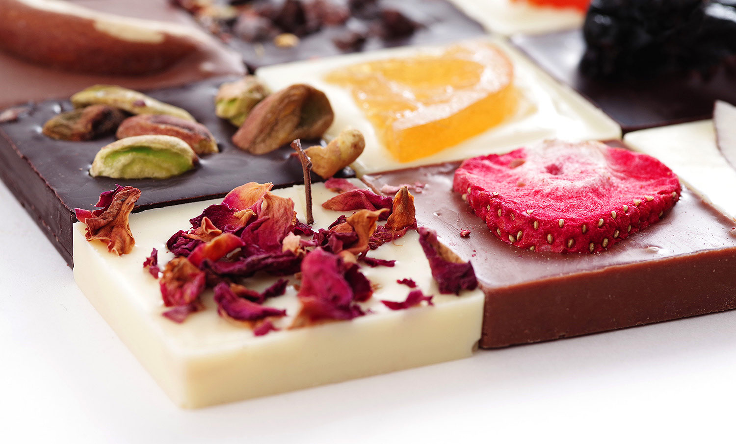 White chocolate with rose petals, milk chocolate with strawberries, white chocolate with orange, black chocolate with pistachios. Gift Altbank.