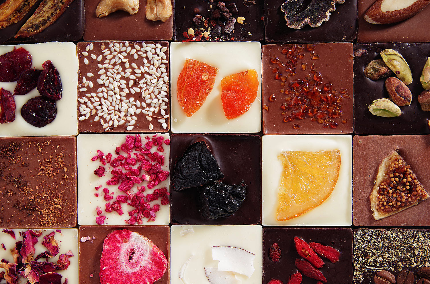 Chocolate background mix: white, black and milk chocolate and unique fillings. Chocolate with raspberries, dried cranberries or a slice of orange, chocolate with salted pistachios, strawberries or rose petals. 20 flavors for 2020.