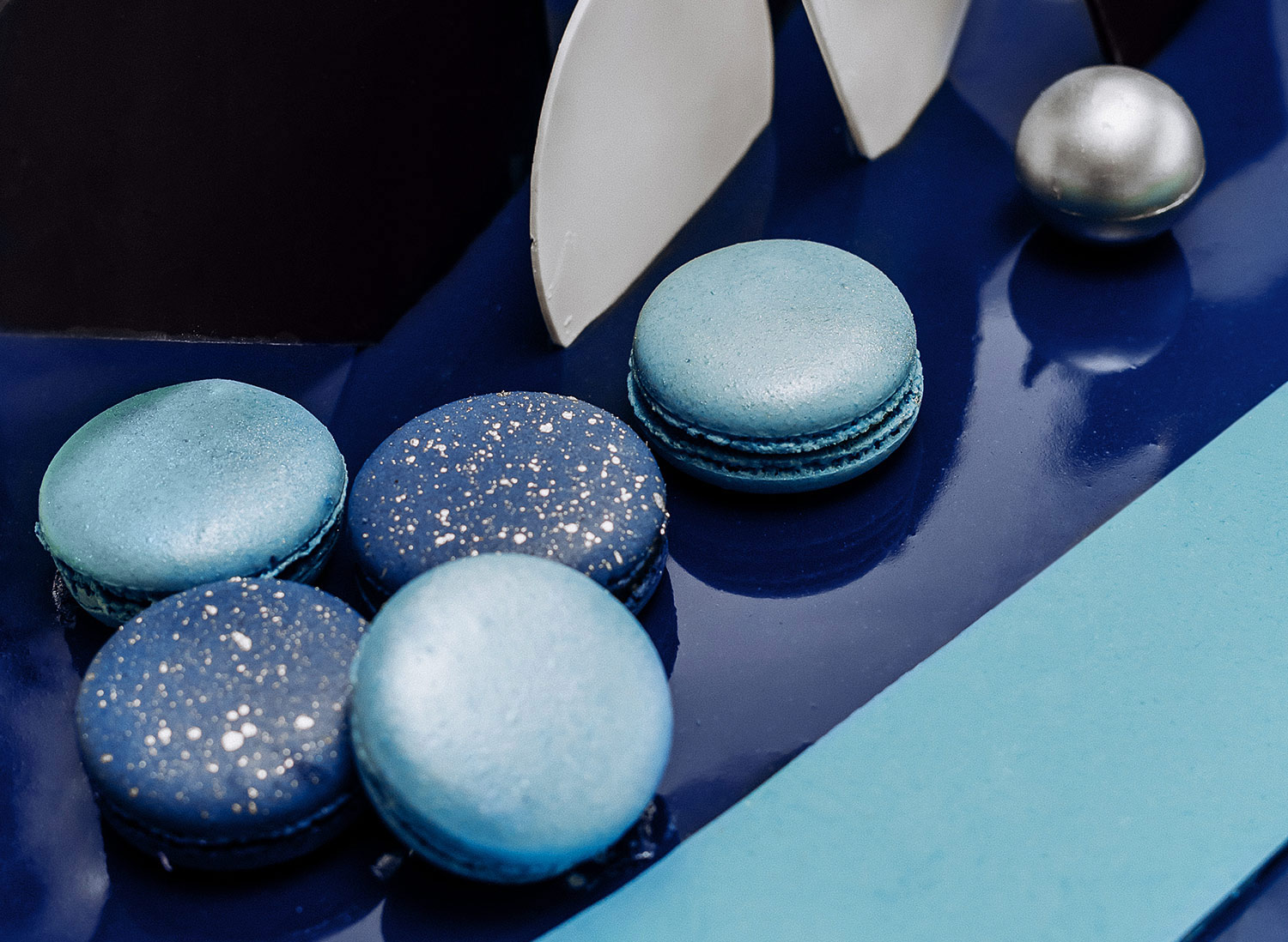 Macarons and geometric shapes made of chocolate on the cake.